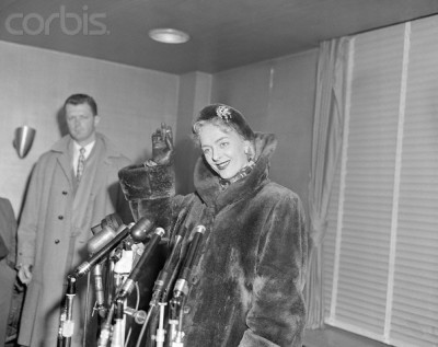Christine Jorgensen arriving at Idlewild Airport, New York, with police guards on February 12,  1953 (Source: corbisimages.com)